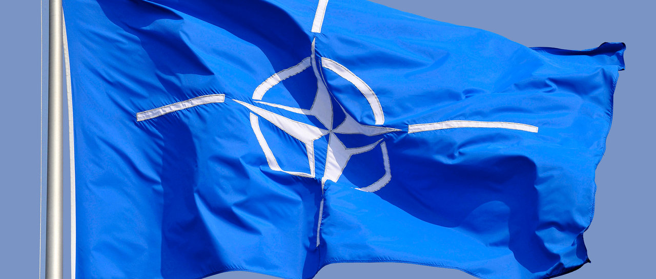 Flag of the North Atlantic Treaty Organization in front of the headquarters in Brussels.